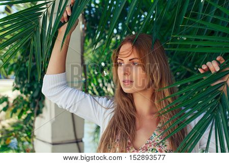 Beautiful caucasian girl on a vacation looking through palm leafs summer day
