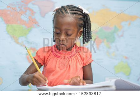Cute little African American preschool girl writing in a classroom