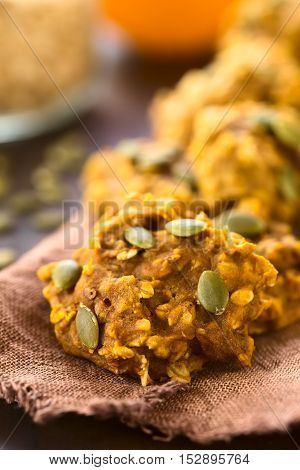 Pumpkin and oatmeal drop cookies with pumpkin seeds on top photographed with natural light (Selective Focus Focus one third into the image)