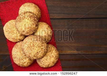 Homemade snickerdoodle cookies with cinnamon and sugar coating photographed overhead on dark wood with natural light (Selective Focus Focus on the cookies on the top)