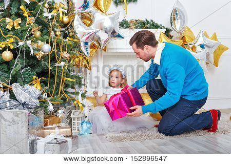 Father and daughter putting gifts under the Christmas tree. Father holding a gift and a cute little girl sitting on the floor. The festive mood. Family celebration.