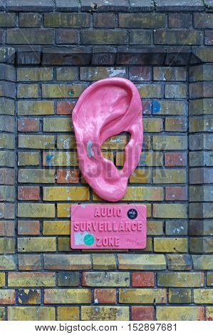LONDON UNITED KINGDOM - NOVEMBER 24: Audio Surveillance Zone in East London on NOVEMBER 24 2013. Big Pink Ear Art Installation by Urban Solid at Brick Lane in London United Kingdom.