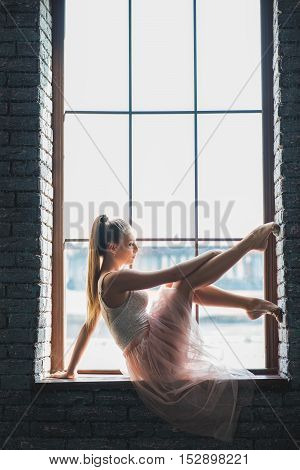 Dancing is visualization of soul. Graceful ballerina posing while sitting on windowsill in dance studio