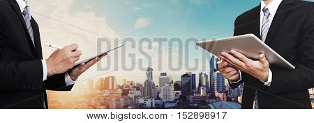Two Businessman working on digital tablet outdoor, and city panoramic background, representing co-workers, partnership in business