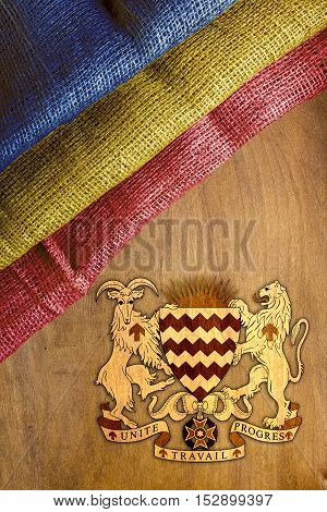 The flag and the coat of arms of the Government of Chad on the wooden background.