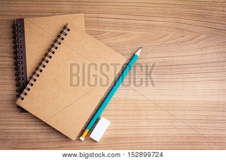 top view of wooden work desk with notebook pencil and eraser