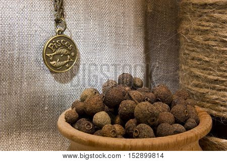 Allspice in a wooden bowl on burlap background