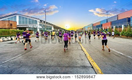 Unidentified marathon athletes running on city road with the yellow sign of traffic car or crosswalk with the industrial Container ship on background