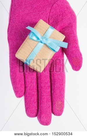 Hand Of Woman In Gloves With Gift For Christmas Or Other Celebration