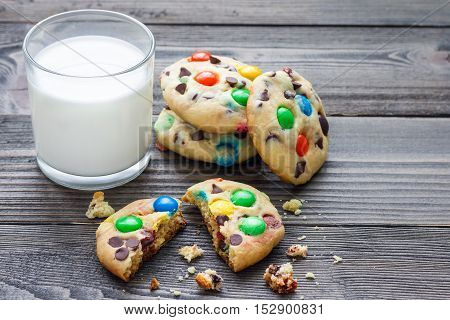 Shortbread cookies with multi-colored candy and chocolate chips served with glass of milk horizontal copy space