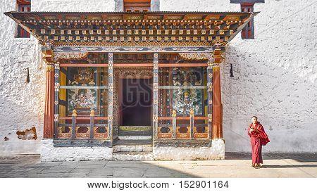 PARO BHUTAN MARCH 02 2016 : the asia man monk walks near the main door tower prayer at Paro Dzong Bhutan