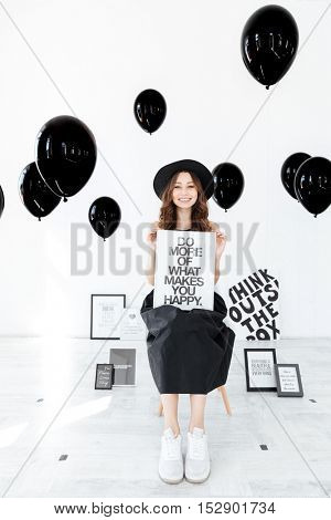 Portrait of cheerful girl with white board over black balloons bakground