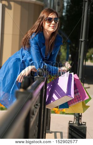 Cheerful young woman is resting after good shopping