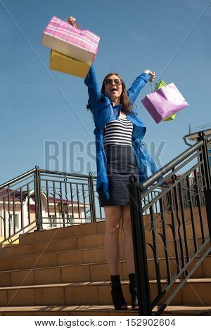Cheerful young woman at the staircase with shopping bags in her raised arms