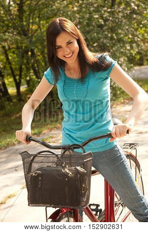 Cheerful young woman in the park with bicycle