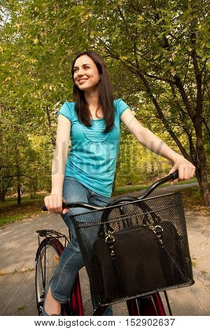 Young charming woman in the park with bicycle