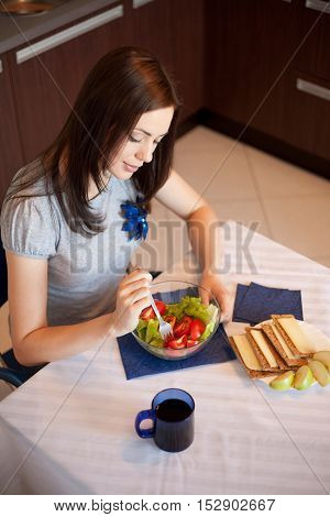 Young woman is eating salad at her kitchen