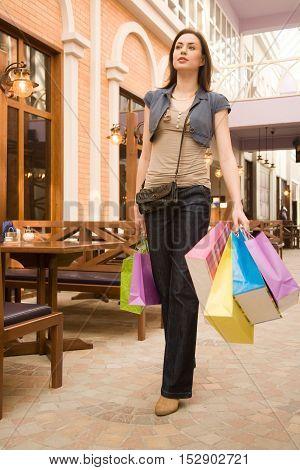 Young woman at shopping mallwalking through small restaurant
