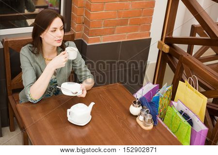 Young woman is drinking her tea in the cafe with her buyings on the chair