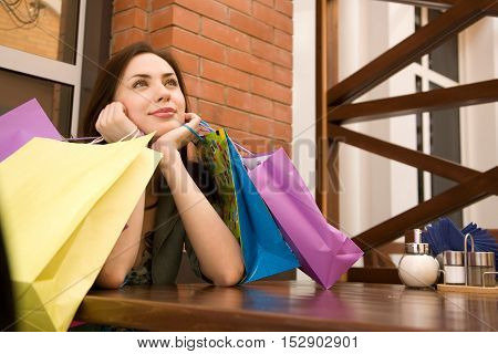 Young woman in the cafe with shopping bags on her table