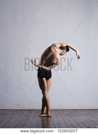 Athletic ballet dancer in a perfect shape performing dramatic dance.