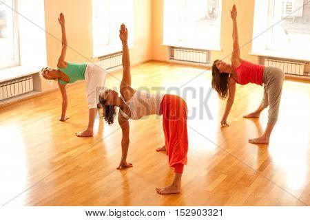 Three women is doing yoga at health club