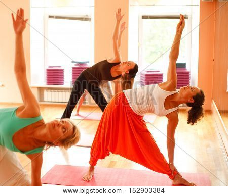 Real yoga instructor at classroom is showing exercise