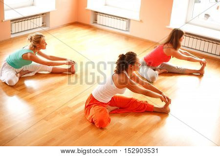 Three women is doing yoga at health club.High angle view
