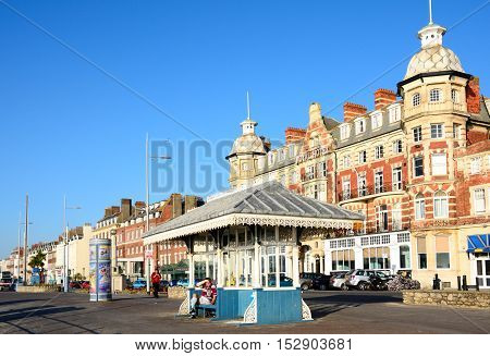 WEYMOUTH, UNITED KINGDOM - JULY 19, 2016 - Covered bench along the Esplanade promenade with the Royal Hotel to the rear Weymouth Dorset England UK Western Europe, July 19, 2016.