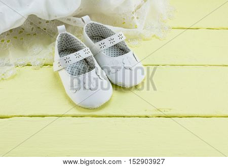 Baby white booties on yellow wood background with white lace dress