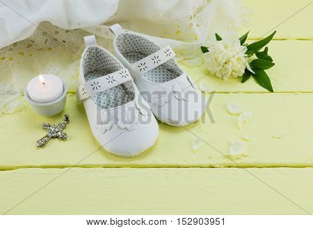 Pair of white baby booties on yellow background with cross and candle