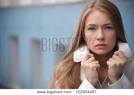 Sad young woman holding collar of her trench coat.Selective focus
