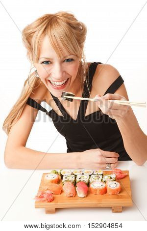 Young smiling woman eating sushi with chopsticks