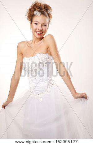 Happy surprised bride is holding dress studio shoot