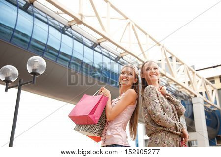 Two young women with shopping bags outdoors.Low angle view