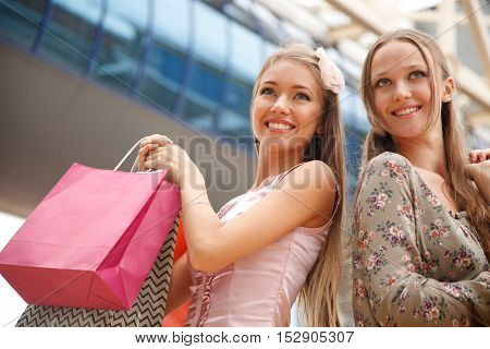 Two young women with shopping bags outdoors