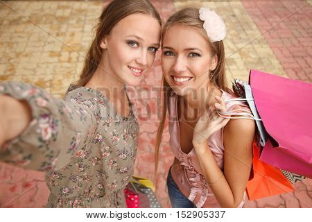 Two girls - shopaholics are taking pictures of themselves. High angle view. Shoot looks like its taken from their camera