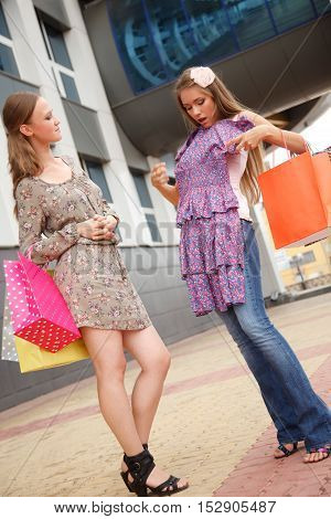 Two girls with shopping bags standing on the streetone of the girls envy of new dress another girl
