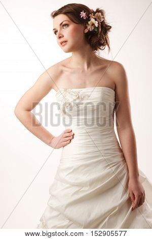 The lovely bride looks upwards and holding a hand on her waist.Modern hairstyle with flowers
