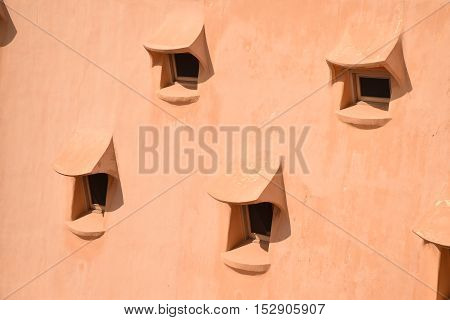 Array of small windows on an organic textured roof in warm colours on a sunny day