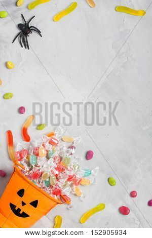 Halloween orange bucket with face with candies inside and rubber spider on gray concrete background vertical orientation