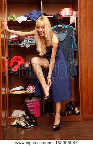 Sensual young woman is putting her shoes on