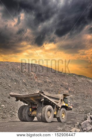 Heavy dump truck on the iron ore opencast on stormy sunset