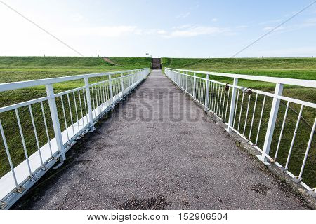 Diminishing Perspective Of Metal Suspension Footbridge Over River