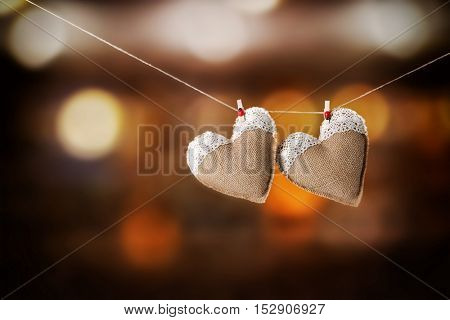 Two hearts hanging on rope against blurred background.