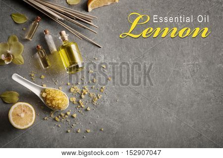 Spa composition with essence on gray background. Text LEMON ESSENTIAL OIL. Spa beauty concept.