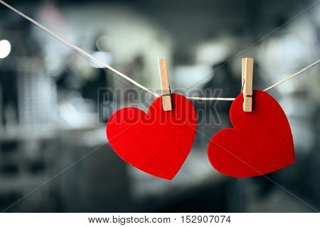 Two red hearts hanging on rope against blurred background.