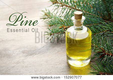 Glass bottle of essence, closeup. Text PINE ESSENTIAL OIL on gray background. Spa beauty concept.