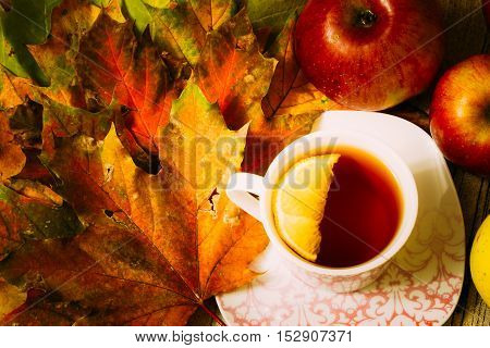 Autumn maple leaves with a cup of tea with lemon on a table red ripe apples. Top view