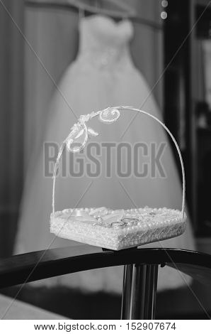Basket with wedding rings on a background of a wedding dress (black and white)